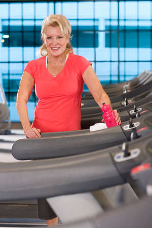 health club: Portrait of smiling senior woman with water bottle on treadmill in health club LANG_EVOIMAGES