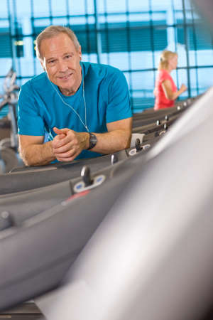 health club: Portrait of smiling man with headphones leaning on treadmill in health club LANG_EVOIMAGES