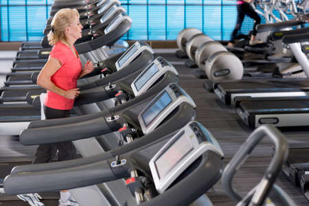 health club: Senior woman running on treadmill in health club LANG_EVOIMAGES