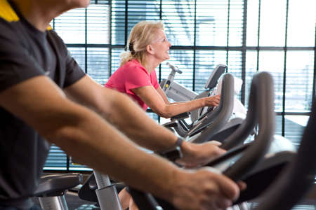 health club: Smiling senior woman riding exercise bike in health club