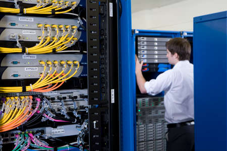 server farm: IT technician checking network server