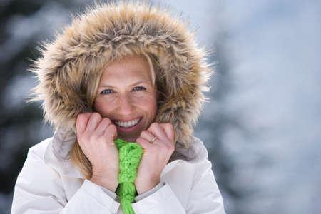 fur hood: Smiling woman in fur hood in snowy outdoors LANG_EVOIMAGES