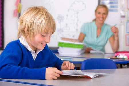 uniforme escolar: Ni�o de la escuela la lectura de libro en el aula