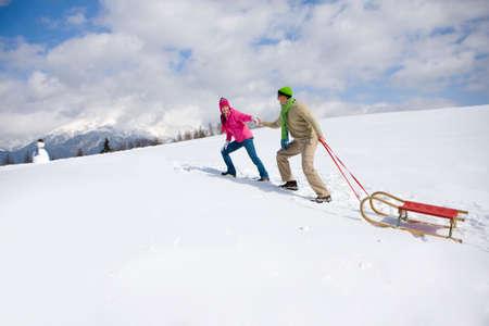 ski walking: Couple walking  up ski slope pulling sled
