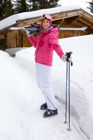 ski lodge: Woman standing in snow near lodge with skis