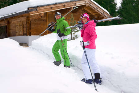 lodge: Couple standing in snow near lodge with skis