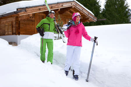 away from it all: Couple standing in snow near lodge with skis