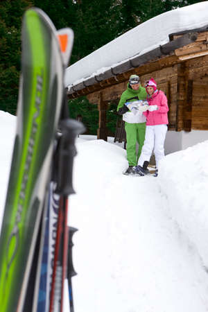 ski lodge: Couple standing in snow near lodge with skis looking at mail LANG_EVOIMAGES