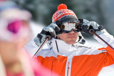 adjusting: Serious skier adjusting goggles