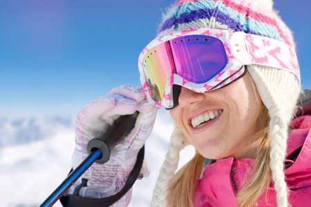 skiing: Smiling skier adjusting goggles LANG_EVOIMAGES