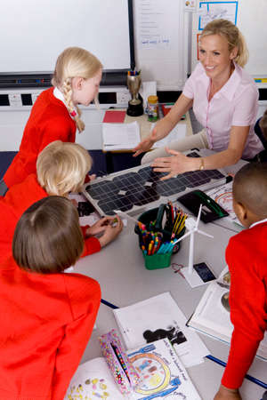 carbon neutral: Teacher and school children looking at solar panel and model wind turbines LANG_EVOIMAGES