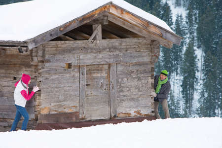 peering: Couple peering around side of weathered wooden cabin in snow