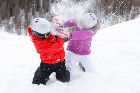 brother sister fight: Brother and sister kneeling in snow and having snowball fight