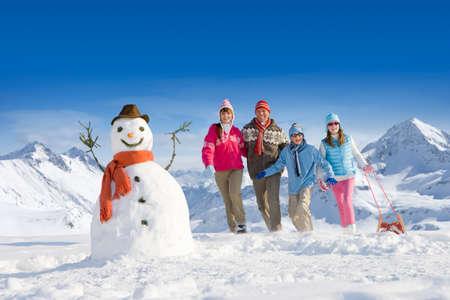 bonhomme de neige: Famille puling traîneau vers bonhomme de neige