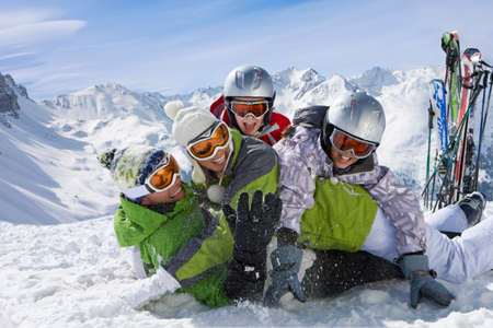 Skis in snow and family having snowball fight on mountain top LANG_EVOIMAGES