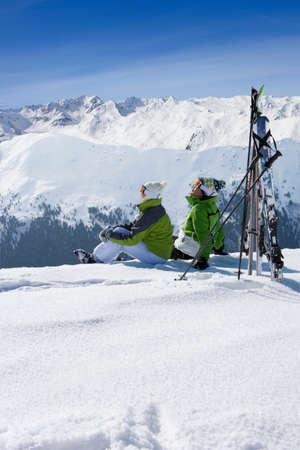cima montagna: Coppia, seduta in neve sulla cima di una montagna con gli sci