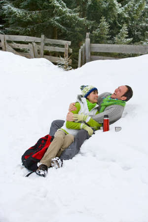 thermos: Laughing couple drinking from thermos and laying in snow together