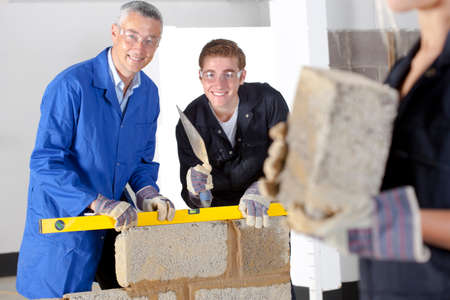 vocational: Teacher talking to student using level in bricklaying vocational school