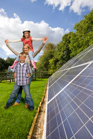 low energy: Happy family standing together near large solar panels
