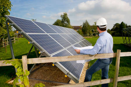 carbon neutral: Technician holding blueprints standing near large solar panels