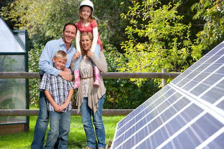 Glückliche Familienstellung der Nähe von großen Solaranlagen
