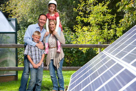 holding family together: Happy family standing near large solar panels