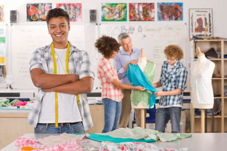 ec: Smiling student sewing clothing in home economics classroom LANG_EVOIMAGES