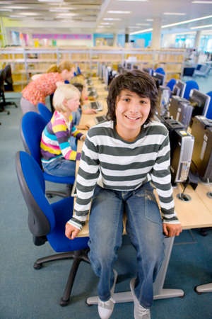 computer lab: Smiling student sitting on desk in computer lab