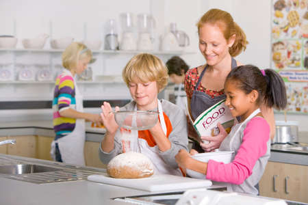 ec: Smiling teacher watching students flouring bread in home economics class