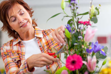 evening class: Smiling woman trimming flowers in floral arrangement in classroom