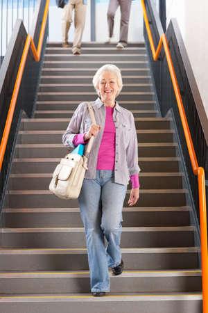 down stairs: Estudiantes adultos caminando por las escaleras en la universidad para llegar a clases nocturnas LANG_EVOIMAGES