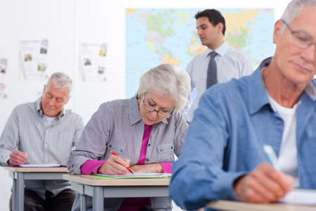 evening class: Adult students taking test in college during evening class