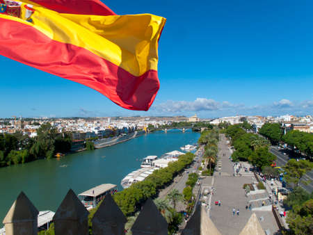 plaza of arms: Spanish flag fluttering with city and river in background, Seville, Spain