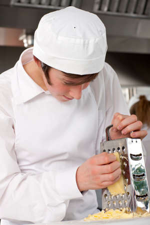 grating: Trainee chef grating cheese in commercial kitchen LANG_EVOIMAGES