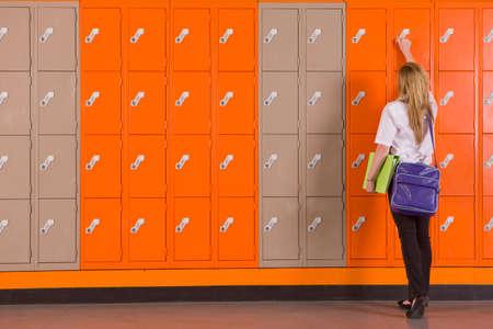 unlocking: Student unlocking school locker LANG_EVOIMAGES