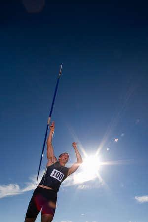 lanzamiento de jabalina: Hombre lanzamiento de jabalina atleta, vista de ángulo bajo (reflejo en la lente) LANG_EVOIMAGES