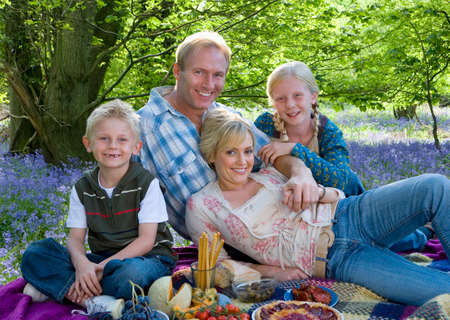 bluebell: Family picnicking in field of bluebell flowers