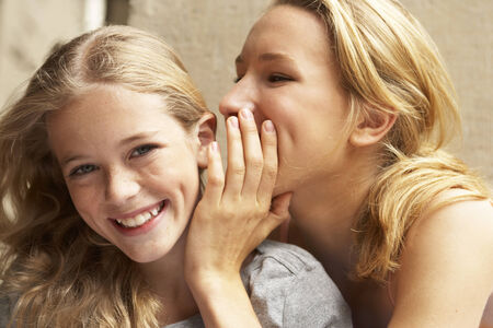 mixed age range: A girl whispering something into another girls ear LANG_EVOIMAGES