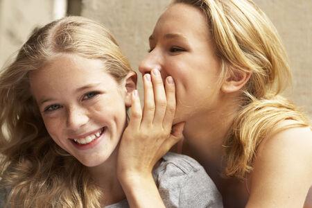 mixed age range: Una muchacha que susurra algo a otra oreja ni�as