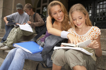 mixed age range: Young male and female students studying on the steps LANG_EVOIMAGES