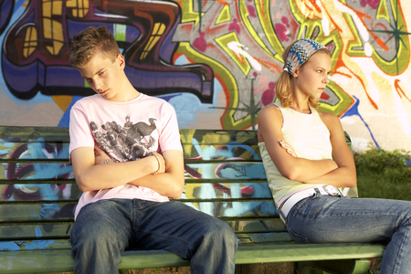 sullen: Young couple sitting at opposite ends of a bench