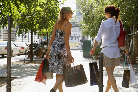 two persons only: Two woman walking on the street carrying shopping bags LANG_EVOIMAGES
