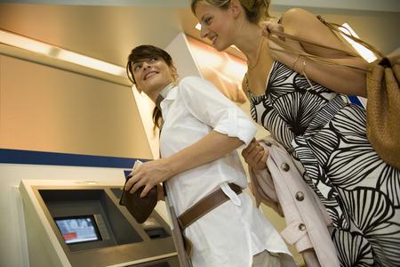 cash dispenser: Women at an ATM machine