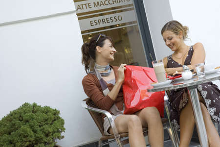 two persons only: Two women going through a shopping bag at a coffee store