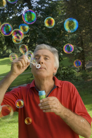 blowing bubbles: A senior adult playing with bubbles