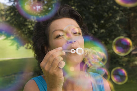 blowing bubbles: A mature adult playing with bubbles