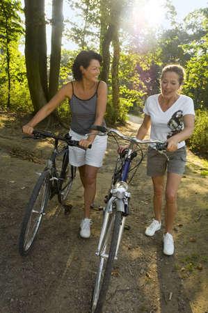 ciclos: Dos mujeres caminando con ciclos