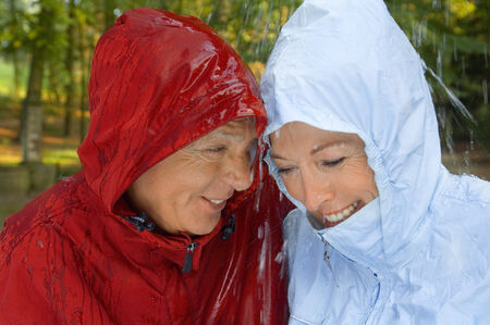 retired couple: A senior couple wearing raincoats in the rain