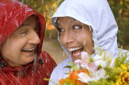 uomo sotto la pioggia: Una coppia senior indossando impermeabili sotto la pioggia