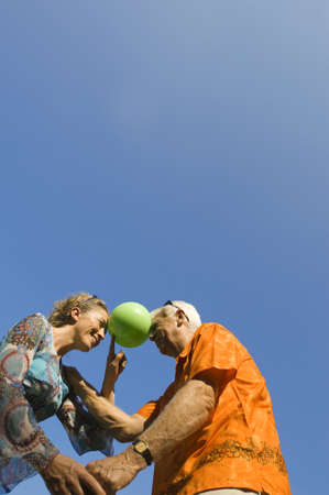 A mature couple with a ball between their heads Imagens